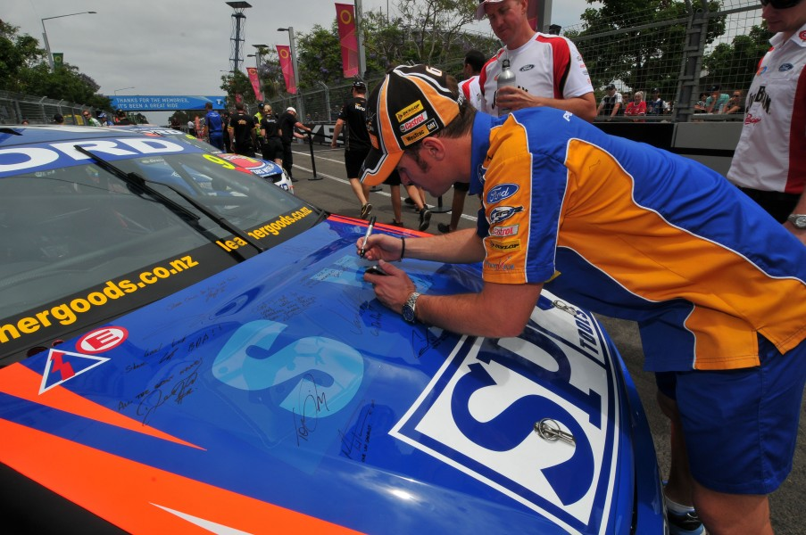 Will Davison of Ford Performance Racing signs the bonnet of the car of Shane Van Gisbergen of Stone Brothers Racing during the Sydney Telstra 500, event 15 of the Australian V8 Supercar Championship Series at the Sydney Olympic Park, Sydney, Queensland, December 02, 2012.